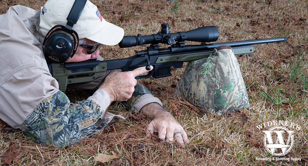a photo of a man shooting a bolt action rifle