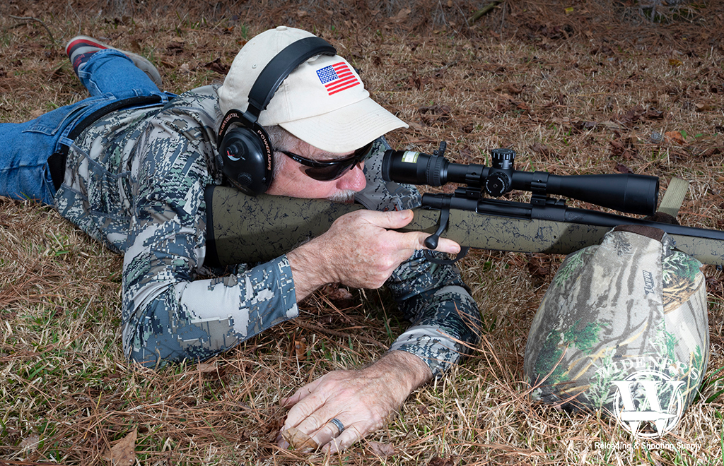 a photo of a man shooting a bolt action hunting rifle