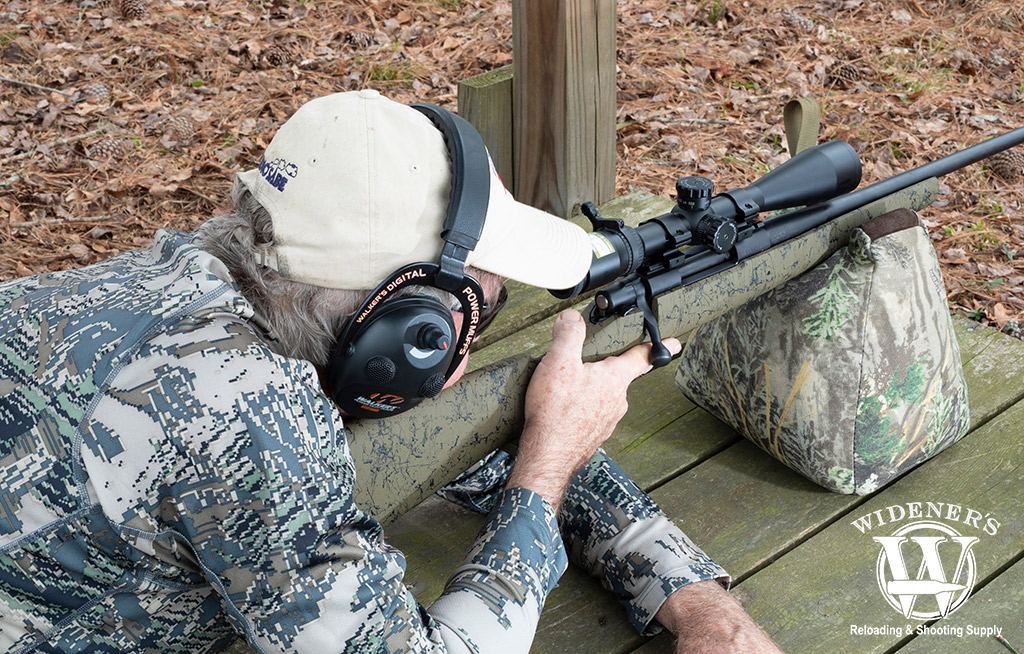 a photo of a man shooting a bolt action rifle and centerfire ammo