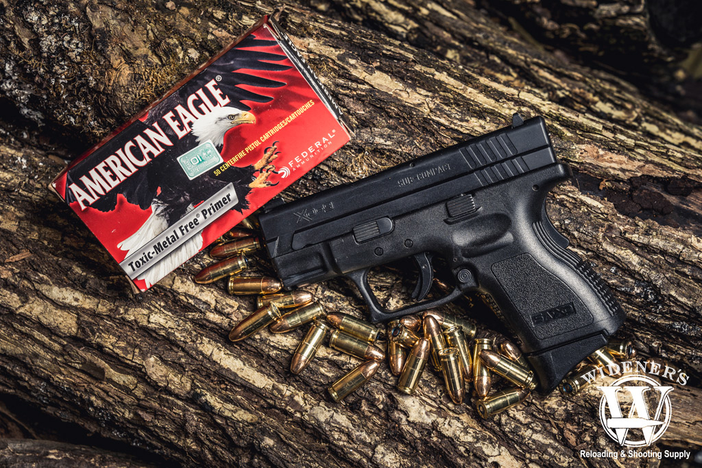 photo of springfield xd 9mm handgun with federal american eagle best 9mm ammo on a log