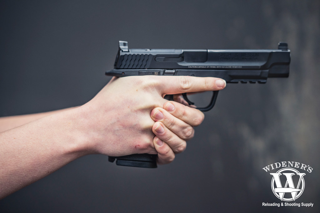 Photo of competition shooting female holding a smith & wesson M&P 9mm pistol