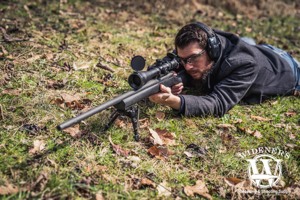 photo of a man shooting a hunting rifle outdoors