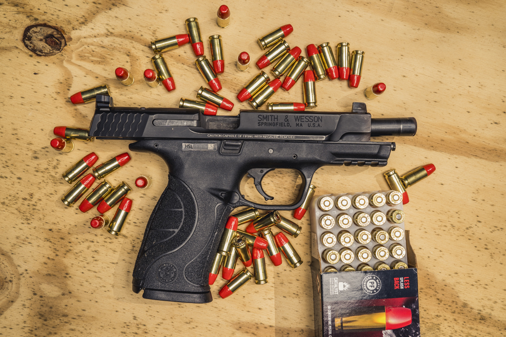 photo of 9mm smith & wesson M&P pistol with federal syntech ammo on a sheet of plywood