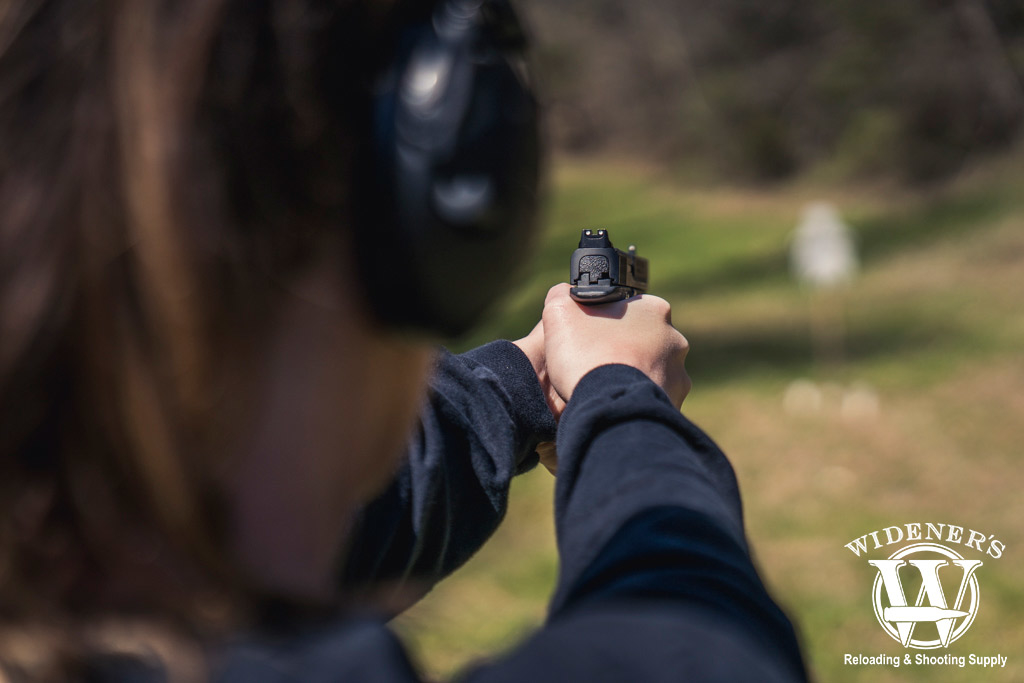 photo of a female competition shooter firing at a steel target outdoors