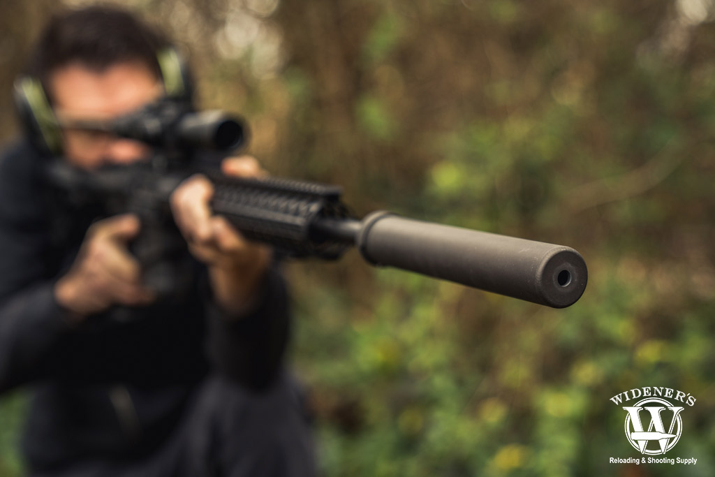 a photo of a man shooting a suppressed ar15 rifle outdoors