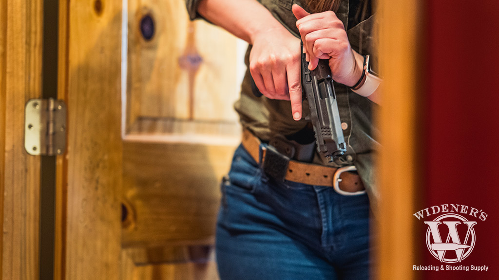 photo of a woman racking the slide on a smith & wesson pistol