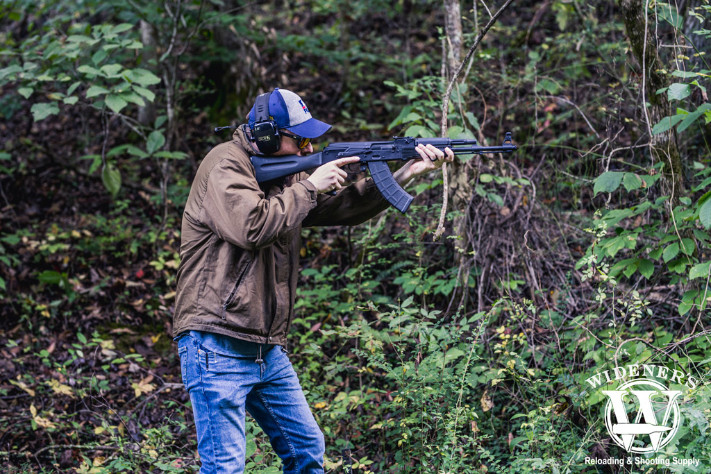 photo of a man shooting an ak47 rifle in the woods illustrating the history of the ak-47