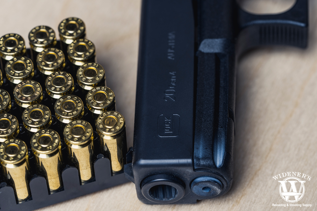 a photo of a glock 20 handgun and 10mm ammo
