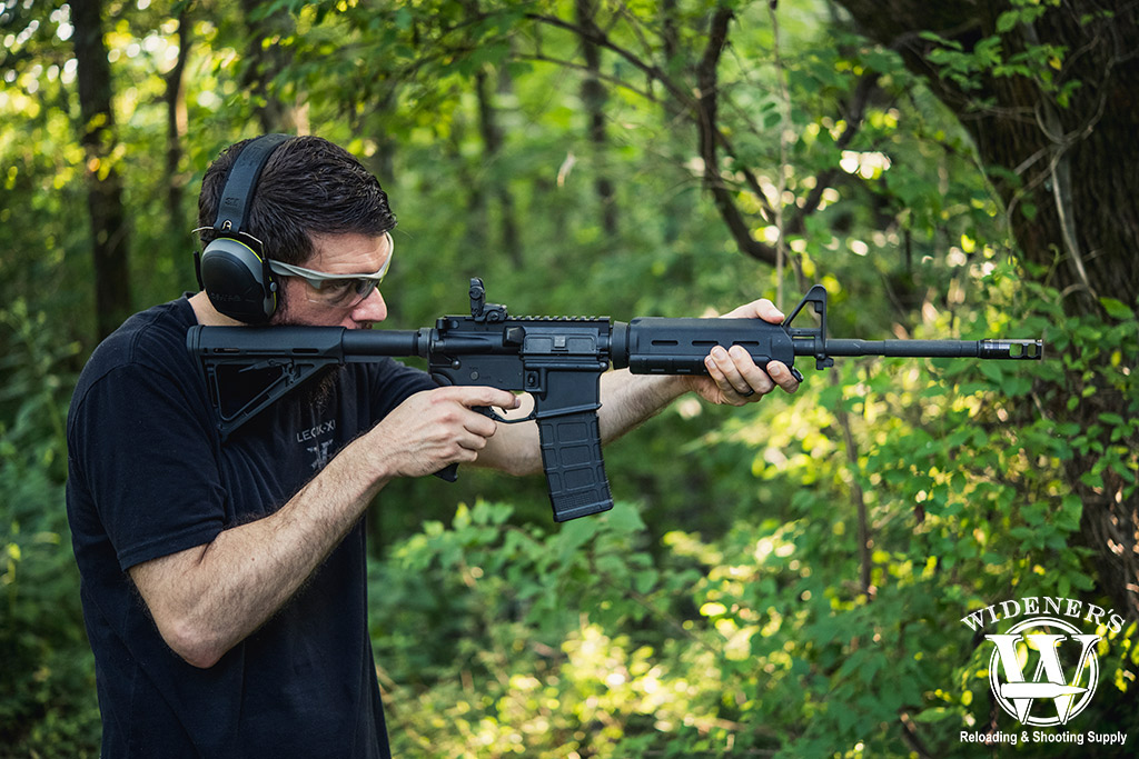 a photo of a man shooting an ar-15 rifle outdoors