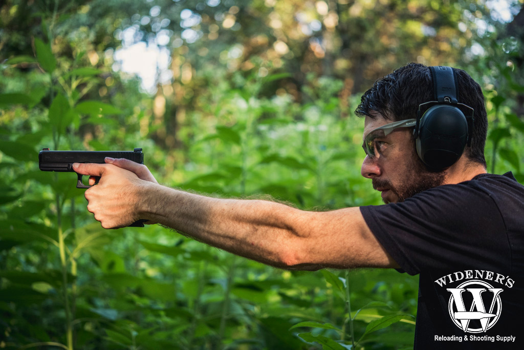 a photo of a man shooting a glock semi auto pistol outdoors
