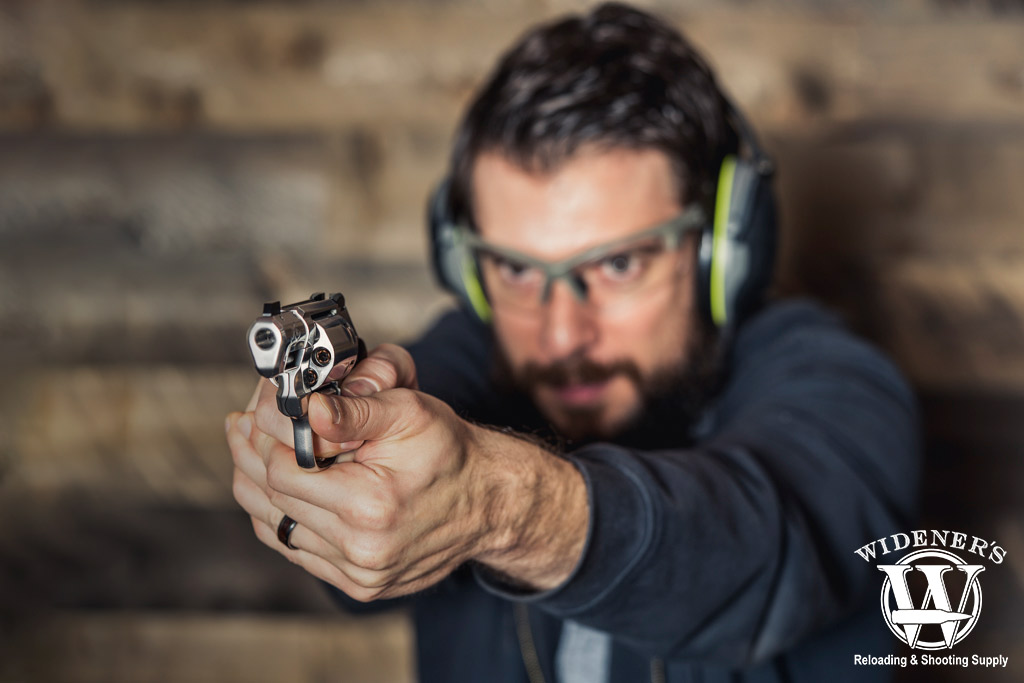 a photo of a man shooting a revolver