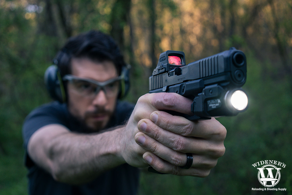 A photo of a man shooting a pistol outdoors red dot vs holographic