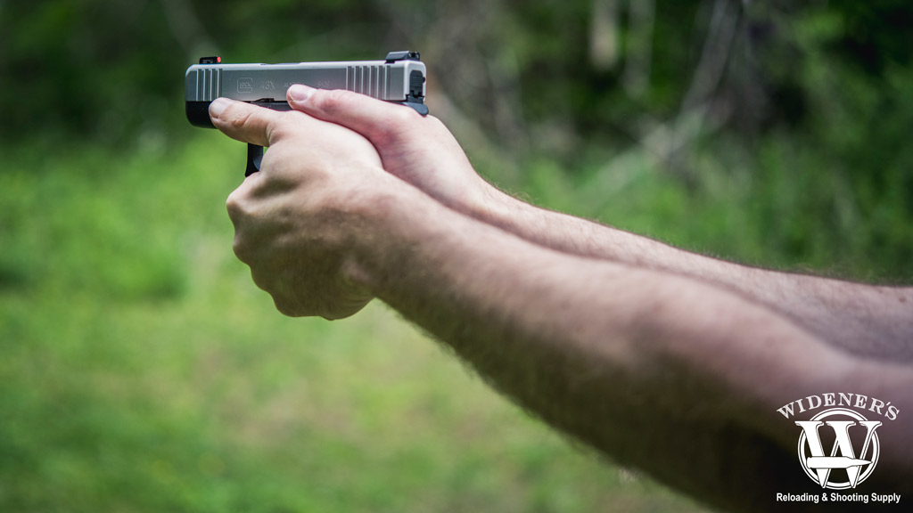 a photo of a man shooting a pistol outdoors