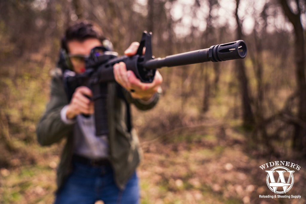 photo of a man shooting an ar-15 rifle outdoors with a flash hider