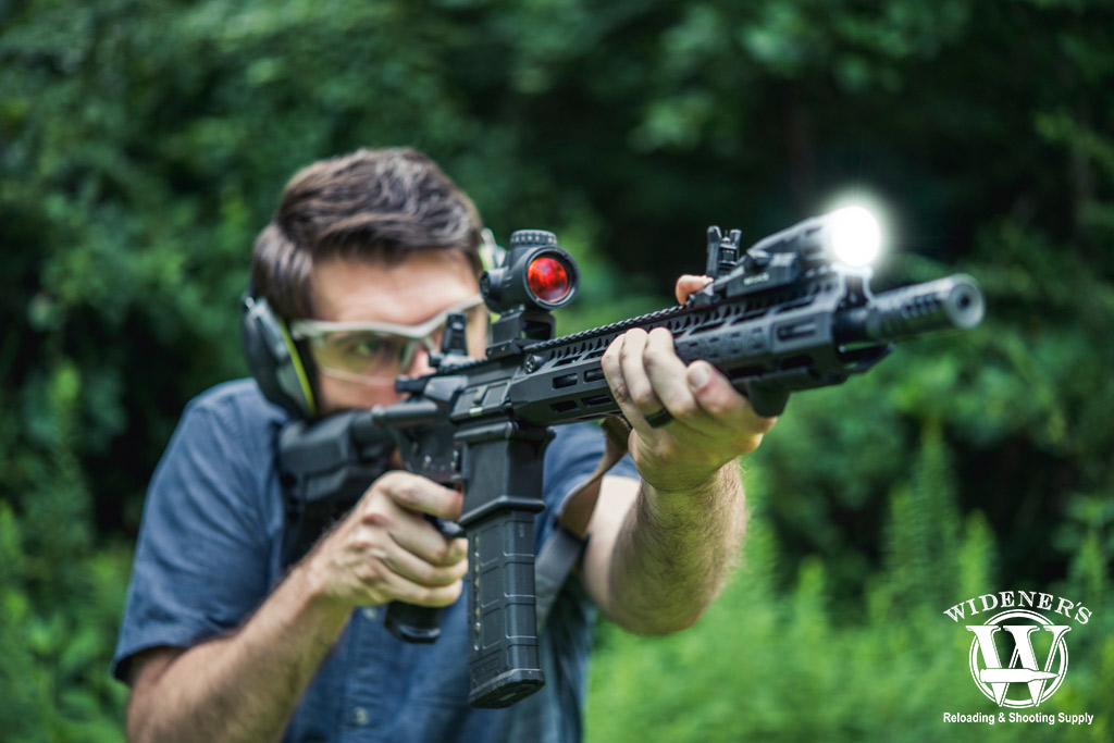 a photo of a man shooting an ar-15 rifle with lower 1/3 co-witness sights