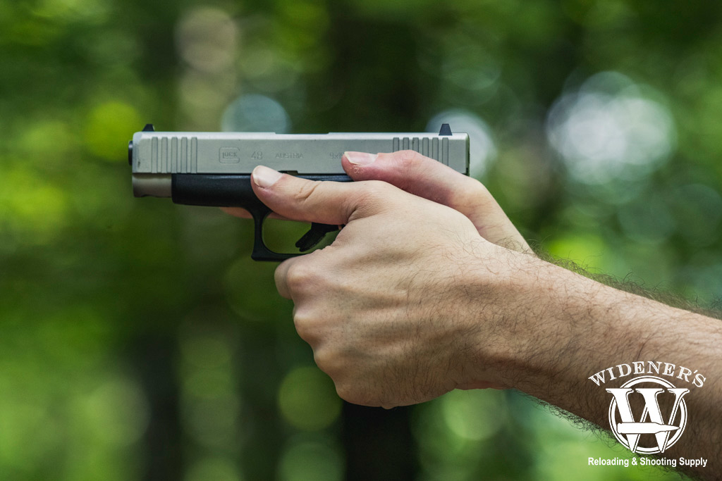 a photo of a man shooting a glock 48 9mm pistol outdoors