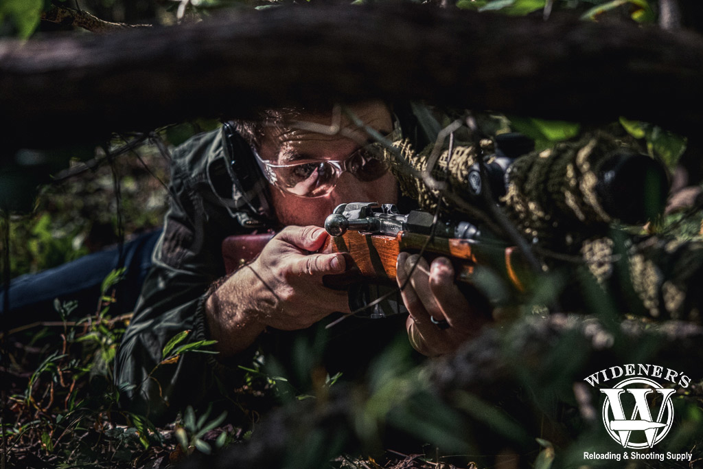 A photo of a man posing in the woods with a sniper rifle