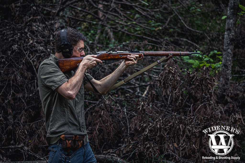 a photo of a man shooting a mosin nagant rifle outdoors