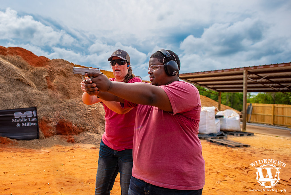 a photo of a female instructor showing a student how to shoot at a gun range
