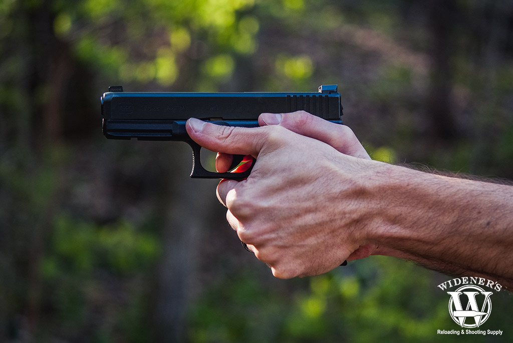 a photo of a man shooting a glock handgun outdoors