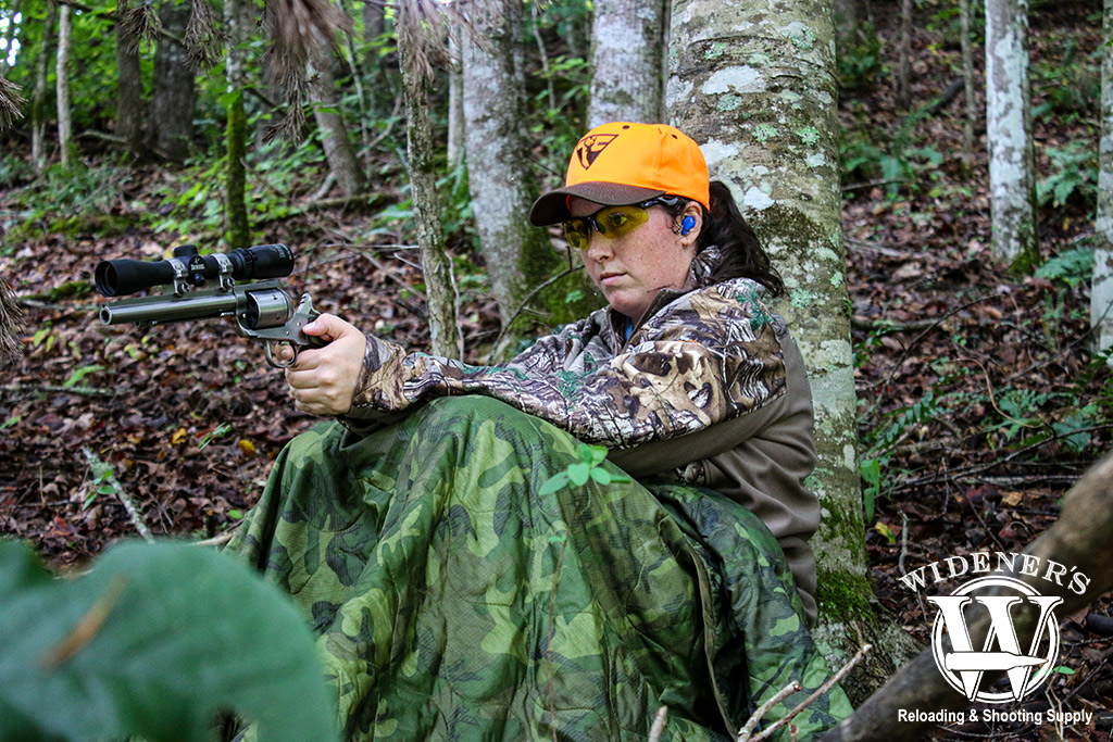 a photo of a female handgun hunting in the woods