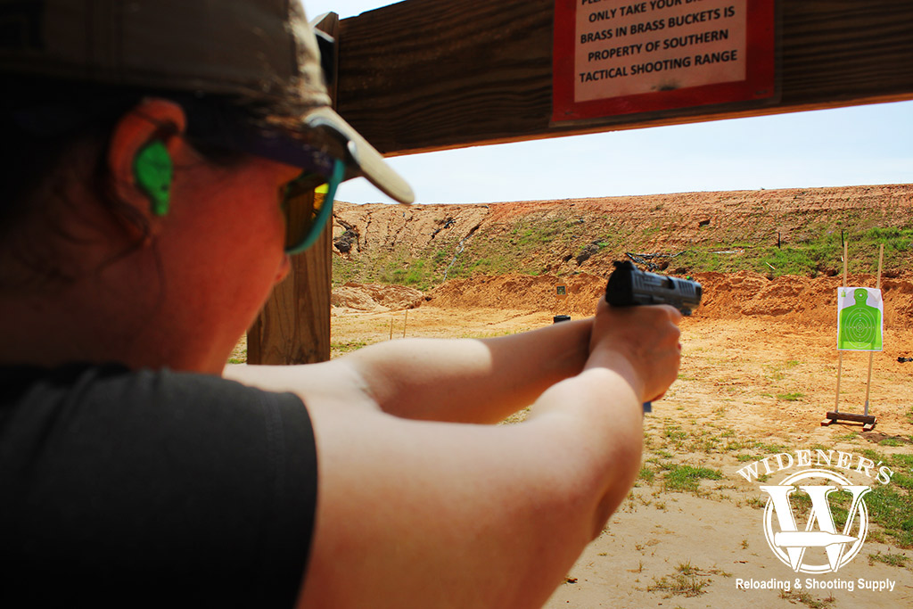 a photo of a female shooting a gun with iron sights at an outdoor range