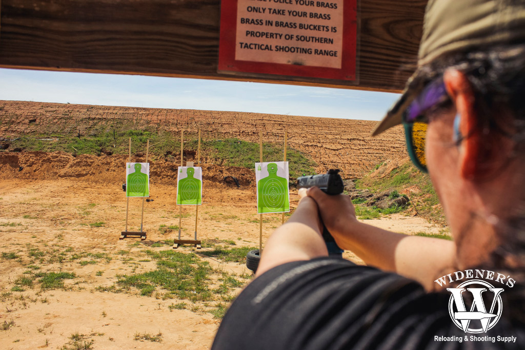 a photo of a female shooting at targets at an outdoor shooting range