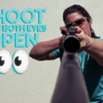 photo of a female shooting a rifle with both eyes open