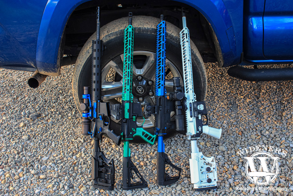 a photo of several custom AR-15 rifles leaning against a blue pickup truck