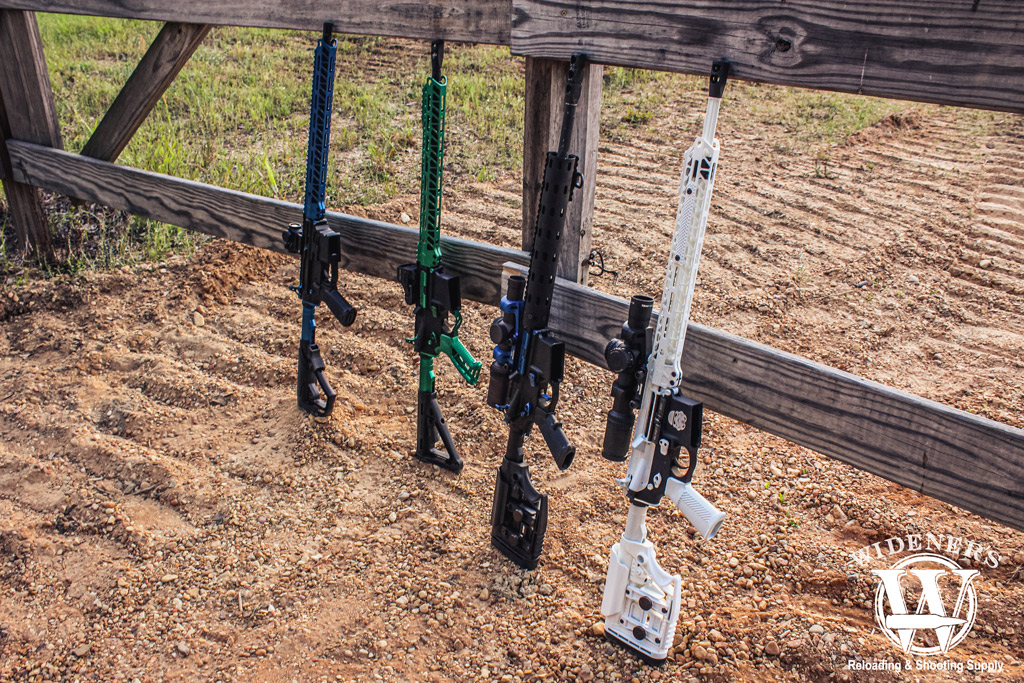 a photo of ar-15 rifles leaning up against a fence