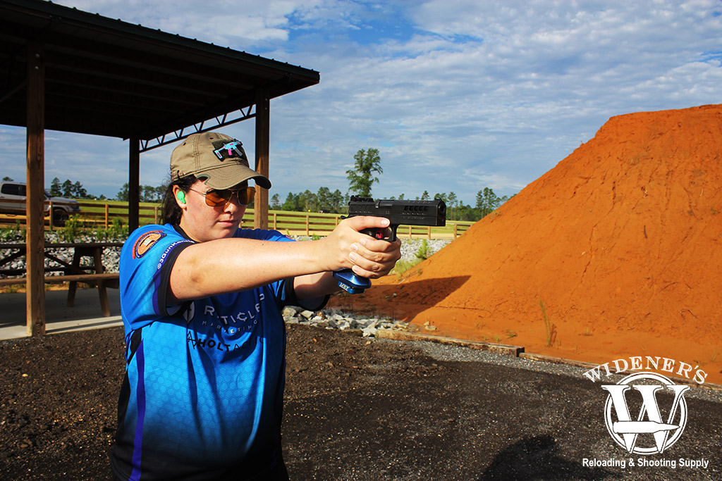 a photo of a female shooter shooting a pistol at an outdoor gun range