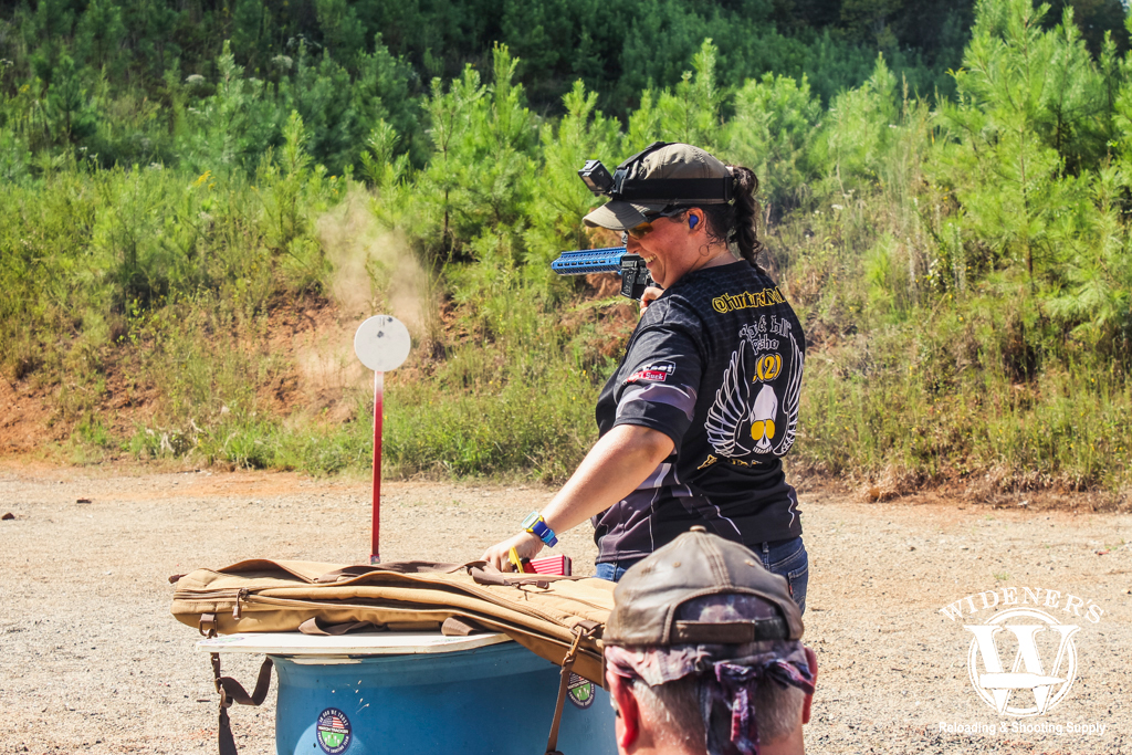 a photo of a female competition shooter reloading at a stage match