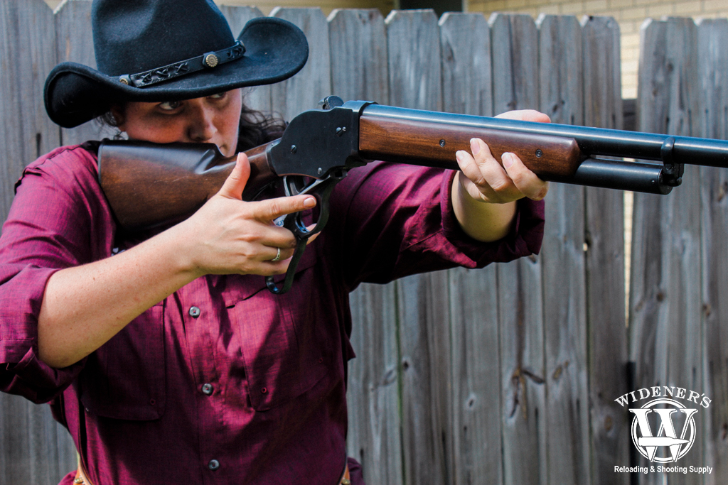 a photo of a female shooting a lever action shotgun