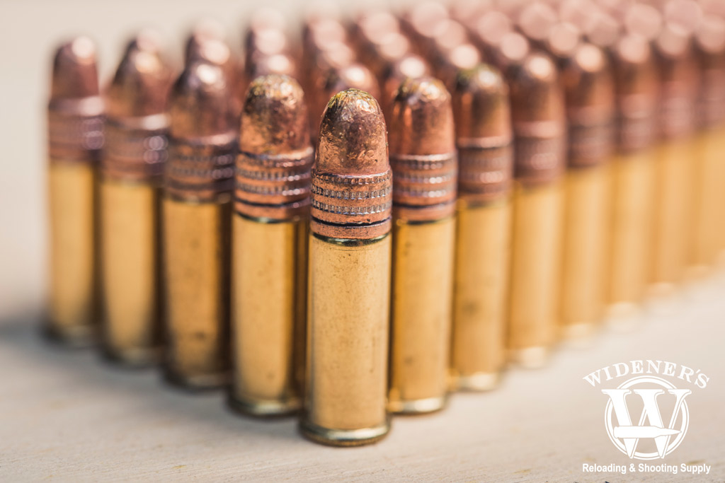 photo of copper plated .22 FMJ bullets stacked side by side on a sheet of plywood