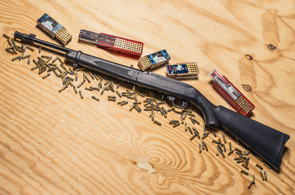 photo of a ruger 10 22 rifle with 22 LR ammo on a sheet of plywood