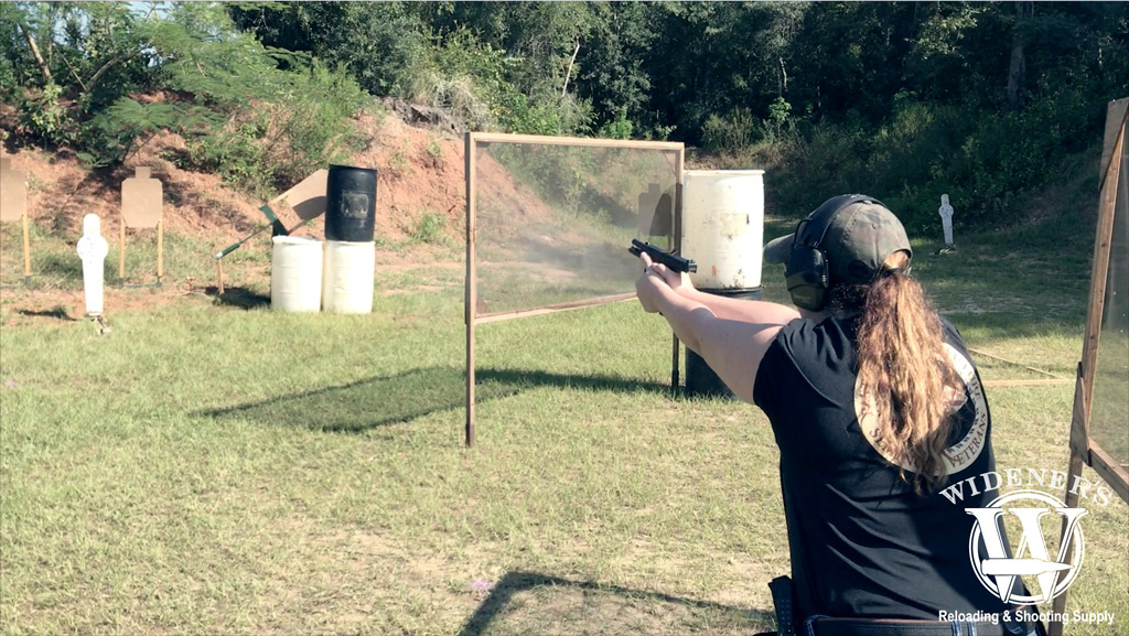a photo of a female competition shooting a pistol at a match