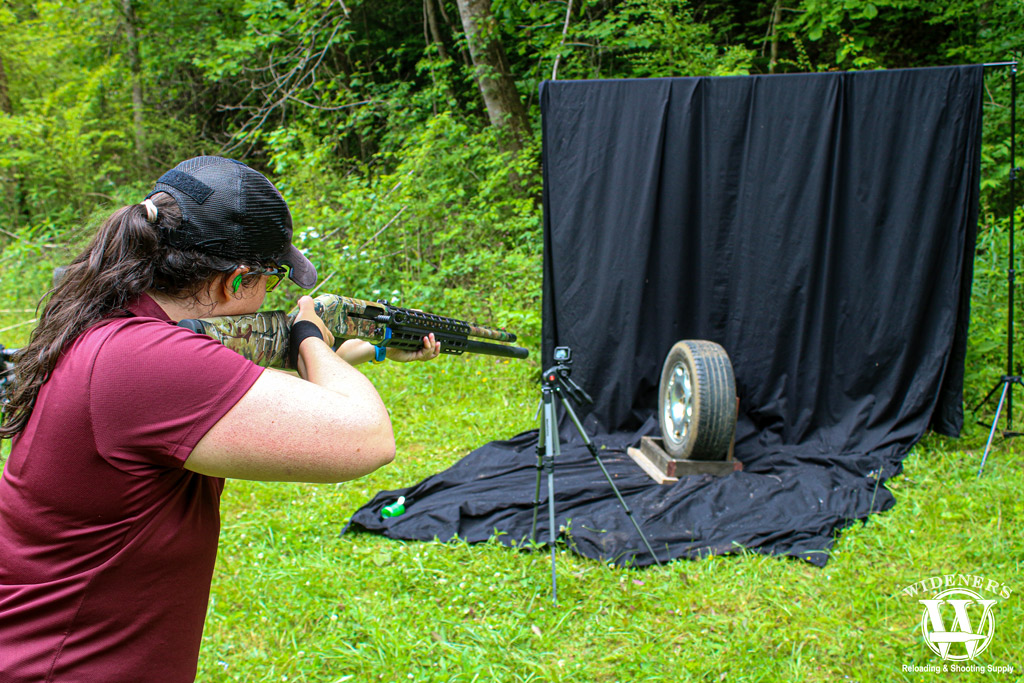 a photo of a woman with a shotgun outdoors