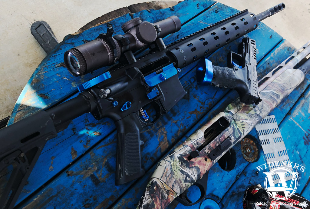 a photo of a ar15 rifle 9mm pistol and 12 gauge shotgun on a table outdoors