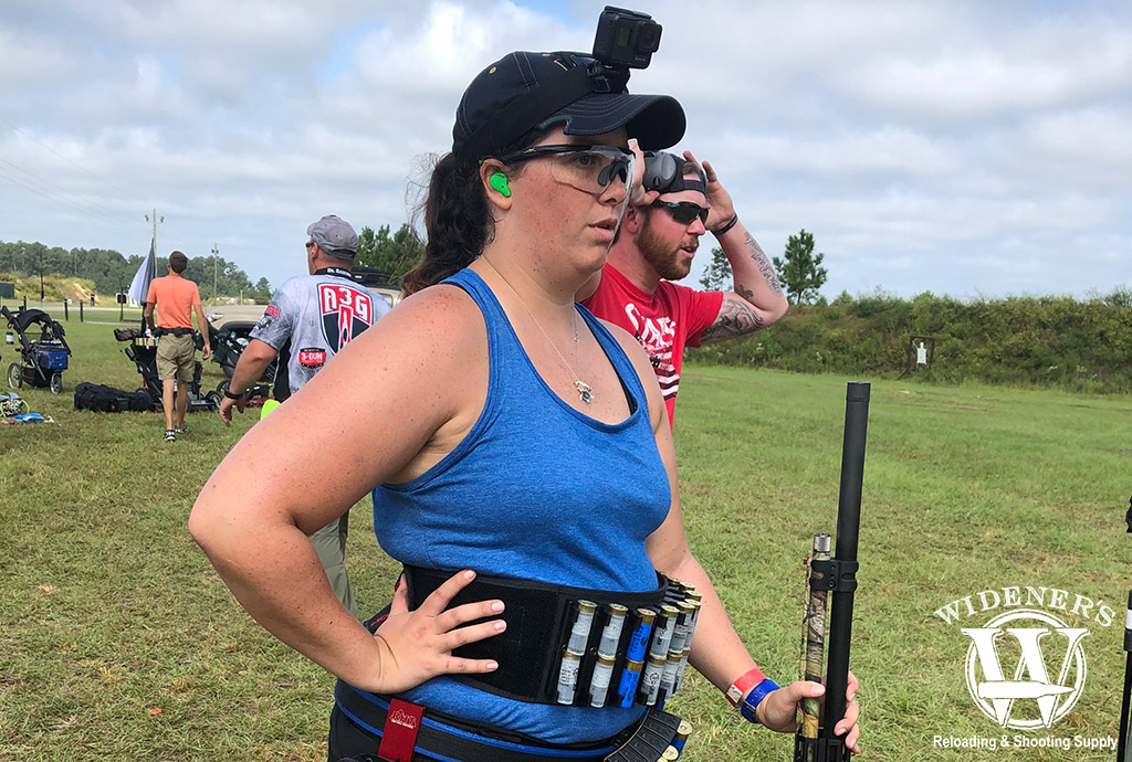 a photo of a female 3 gun competition competitor with a 12 gauge shotgun
