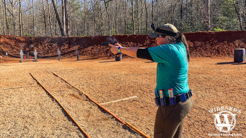a photo of a female shooting a competition pistol outdoors