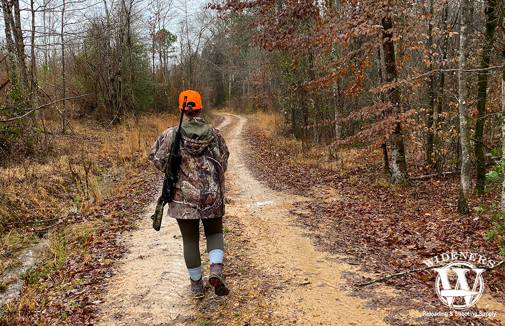 a photo of a female deer hunter in the woods