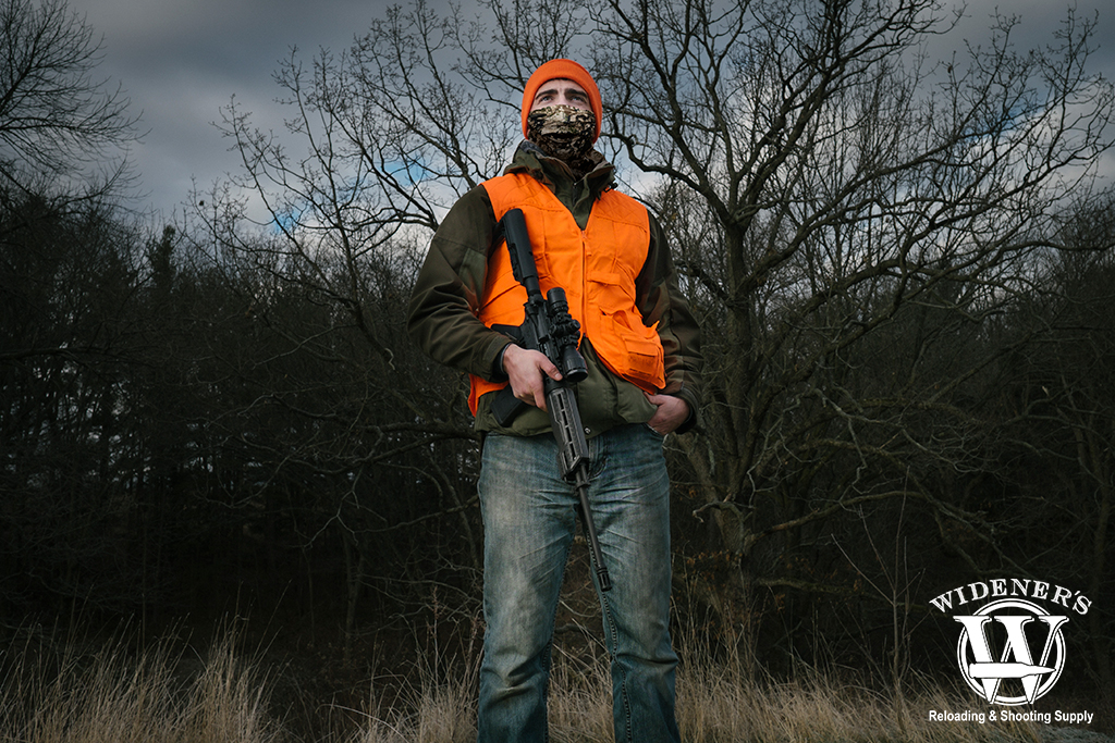 a photo of a man deer hunting in the woods with a rifle
