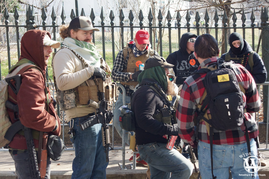 a photo of a group of men open carrying rifles outside