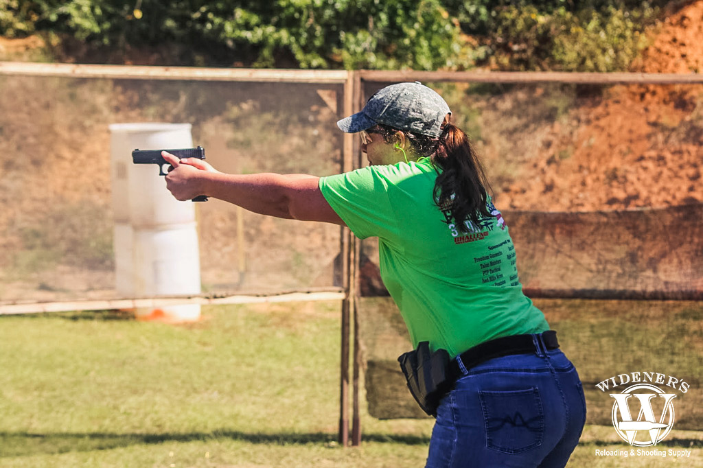 a female competition shooter running at a gun range