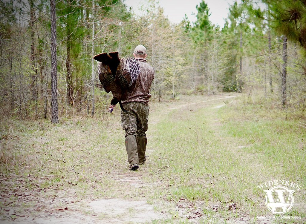 a photo of a man carrying a wild turkey